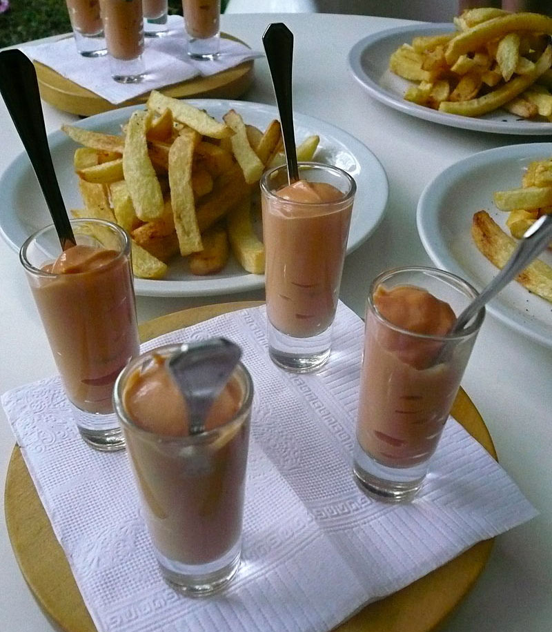 Four glass cups with salsa golf and silver spoons. Plates with fries and more cups with sauce in the background.