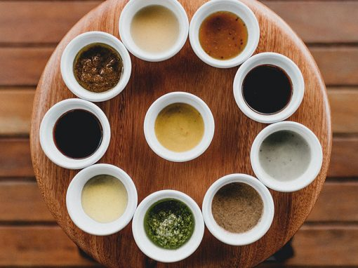 Nine white cups holding a variety of sauces arranged around a wood plate with wood table underneath.