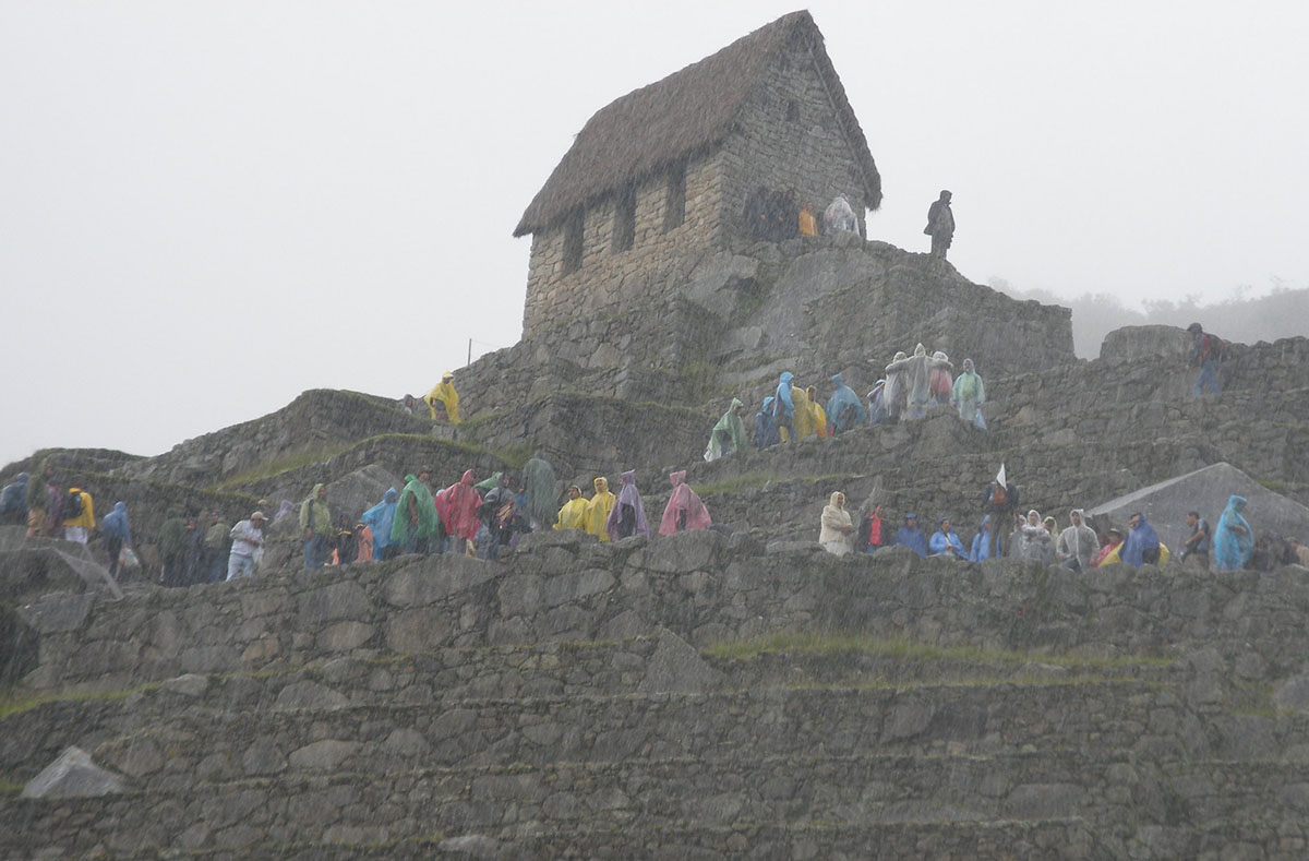 Visitors in colorful ponchos dot the Machu Picchu ruins in the rain and fog.