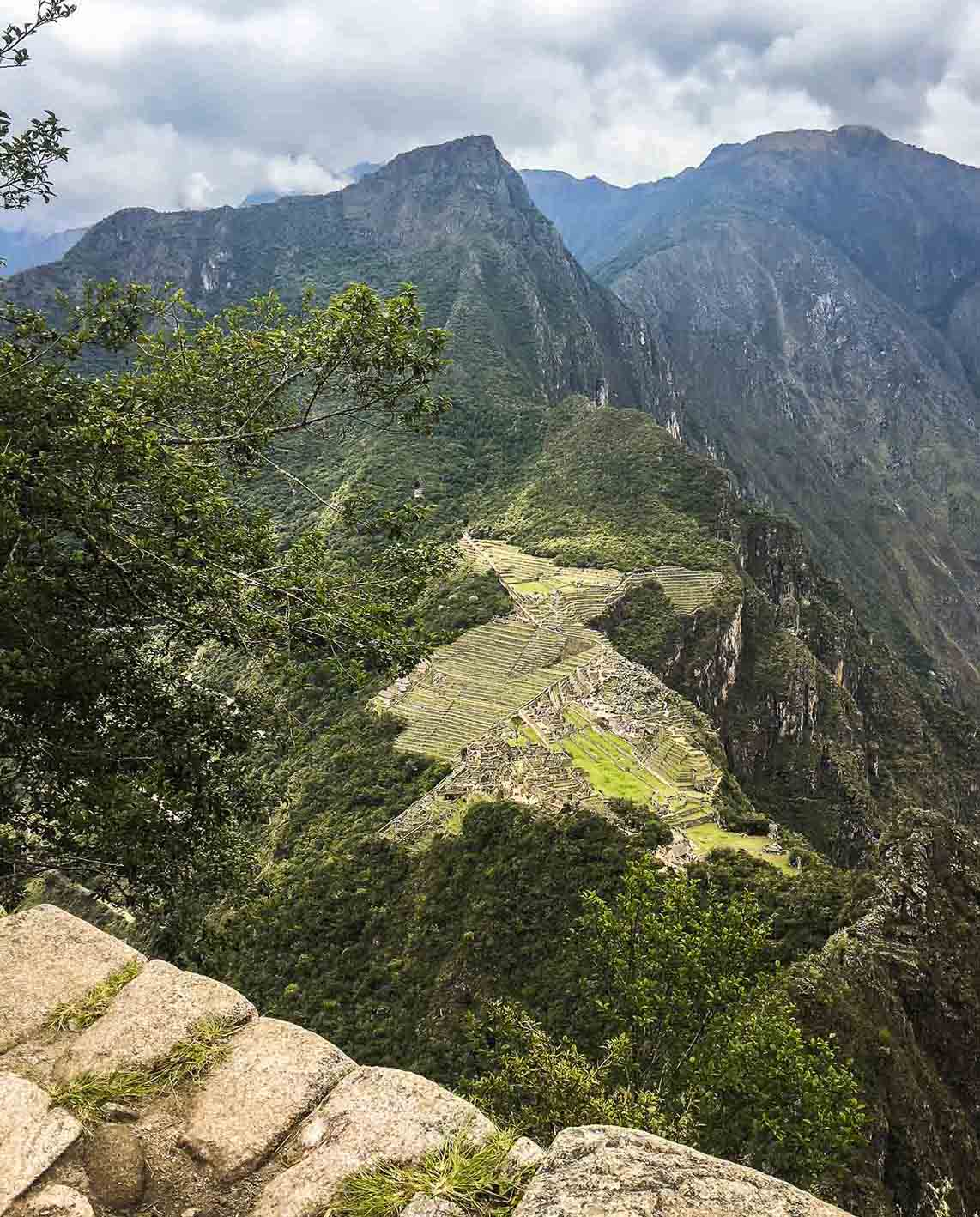 A view looking out at the tall mountain of Machu Picchu from the Hauyna Piccu summit on a cloudy day.