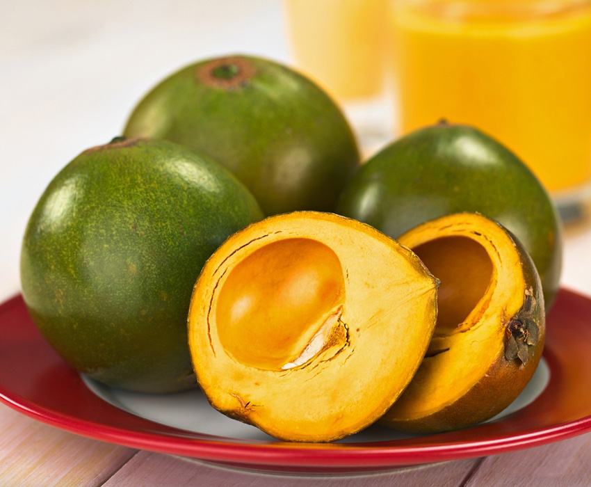Several lucuma on a plate. The lucuma have soft green shells and yellow flesh.
