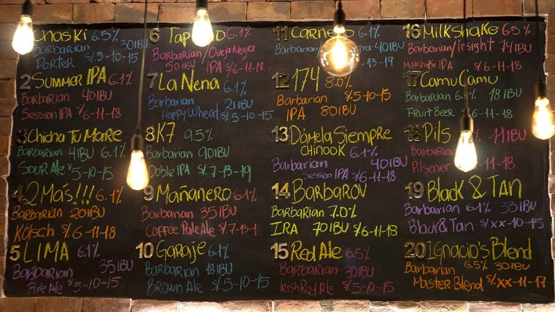Menu with 20 types of draft beer written in colorful chalk on a chalkboard at BarBarian Bar in Lima.