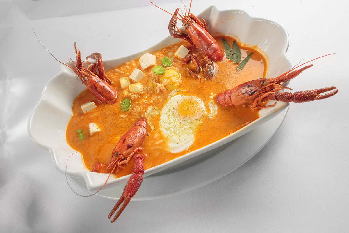 A bowl of the Peruvian soup chupe de camarones with shrimp, an egg, and other foods inside.