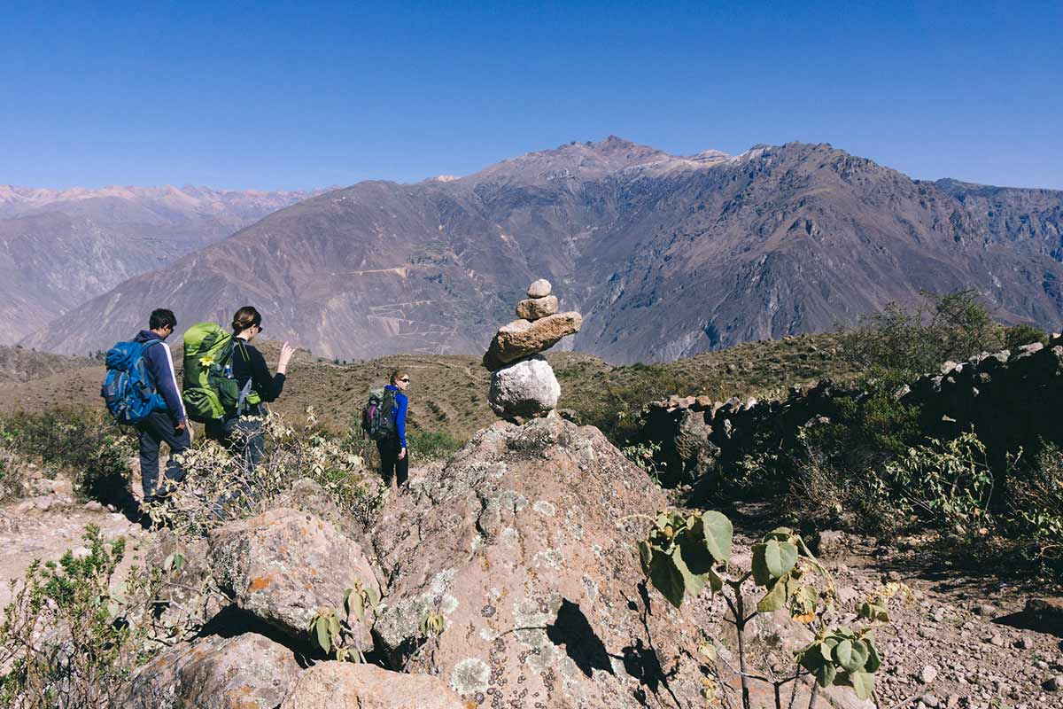 Three trekkers walking with backpacks past rocks into Colca Canyon.
