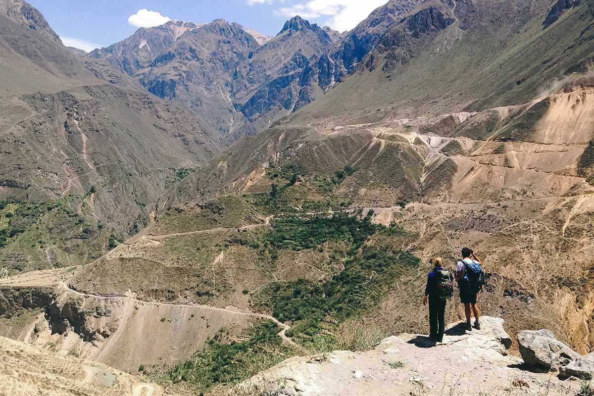 Two trekkers looking over switchback trails in Colca Canyon.