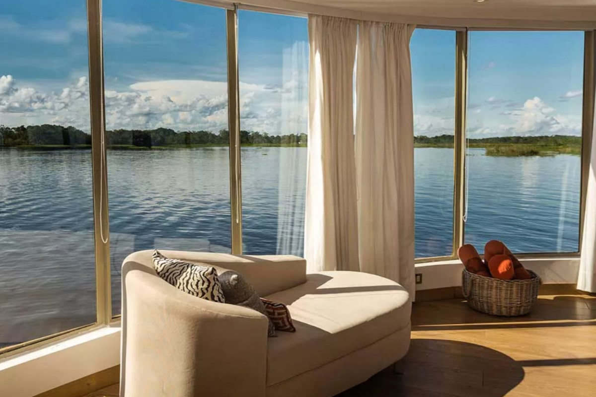 Wall of windows with AMazon river and shore beyond in a guest suite of the Delfin III Cruise