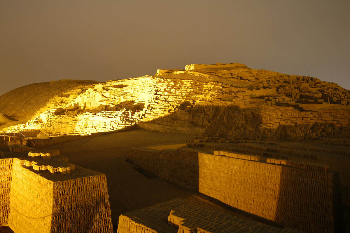 Huaca Pucllana ruins illuminated at night. The lights cast large shadows across the adobe bricks.