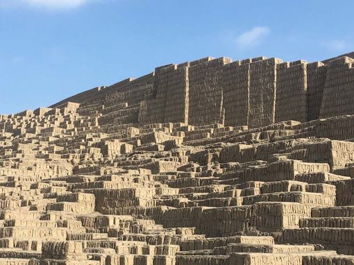The sunlit Huaca Pucllana ruins on clear day with blue skies and offsetting the earthy color of the adobe bricks.