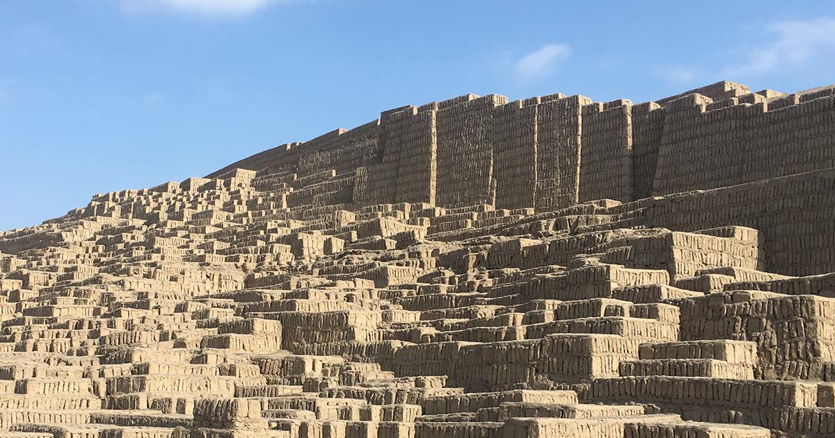 The Huaca Pucllana ruins with blue skies offsetting the earthy color of the adobe bricks.