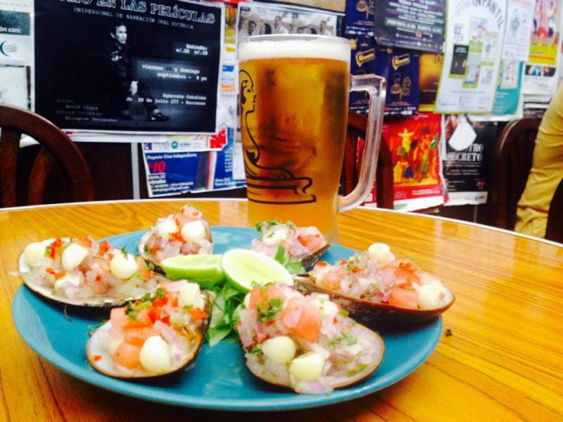 Blue plate with choritos a la chalaca, a Peruvian seafood dish, and a draft beer sitting on a wood table.