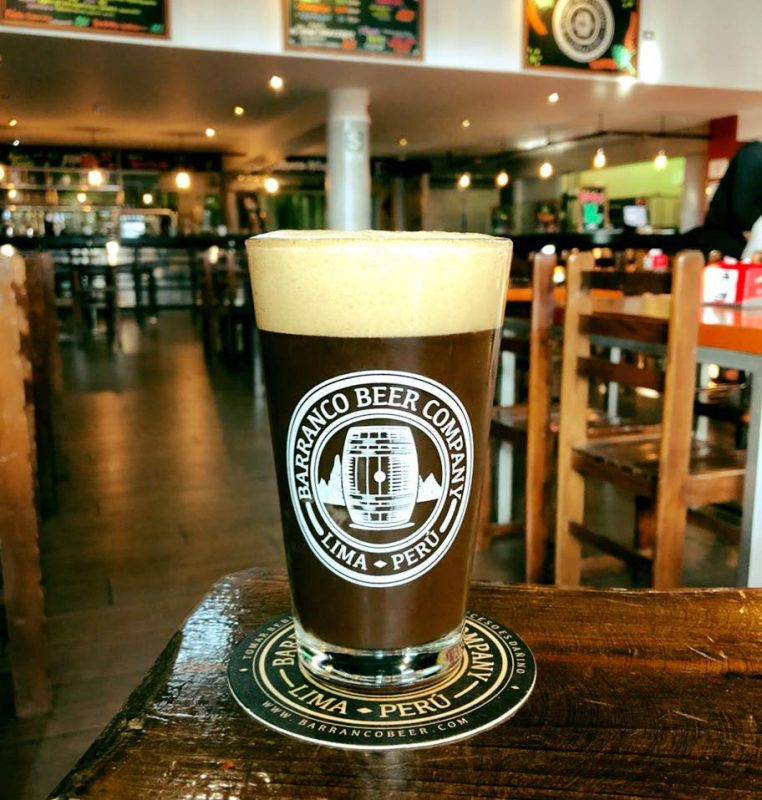 A pint of dark brown beer with foam in a glass at the Barranco Beer Company.