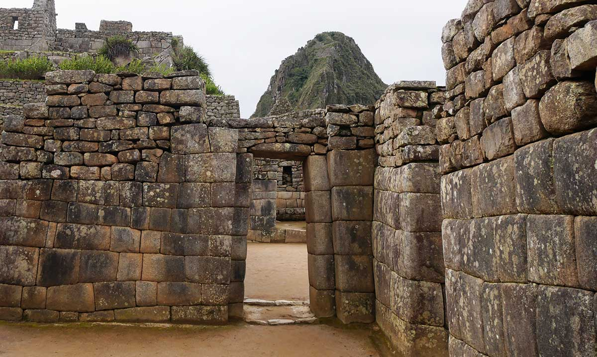 A photo showing the Machu Picchu stonework including an angled Inca doorway. The stones are relatively large and perfectly cut to fit together.