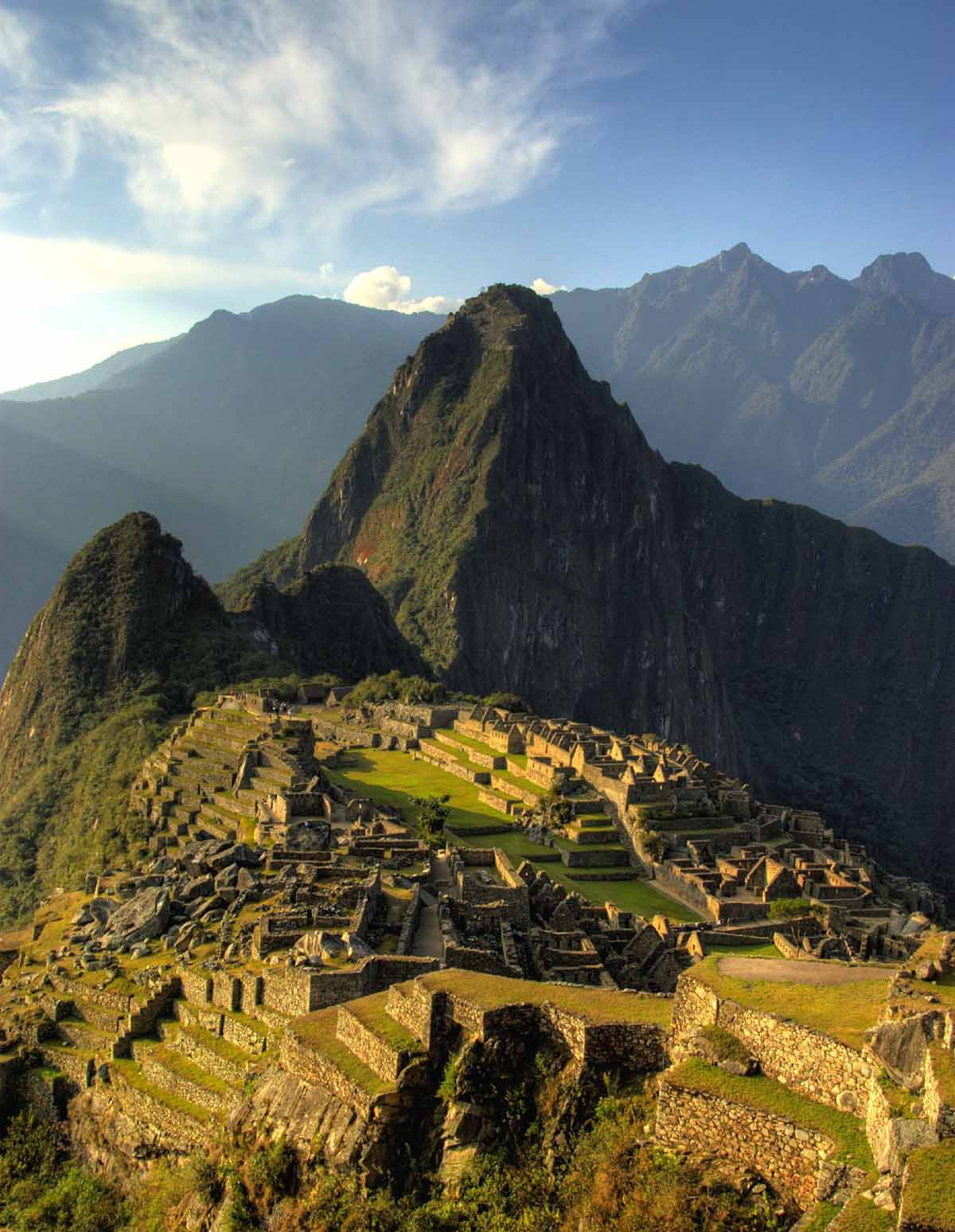 Machu Picchu lit up by the golden light of sunset. The ruins appear warm and glowing and the mountain is partly in the shadow.