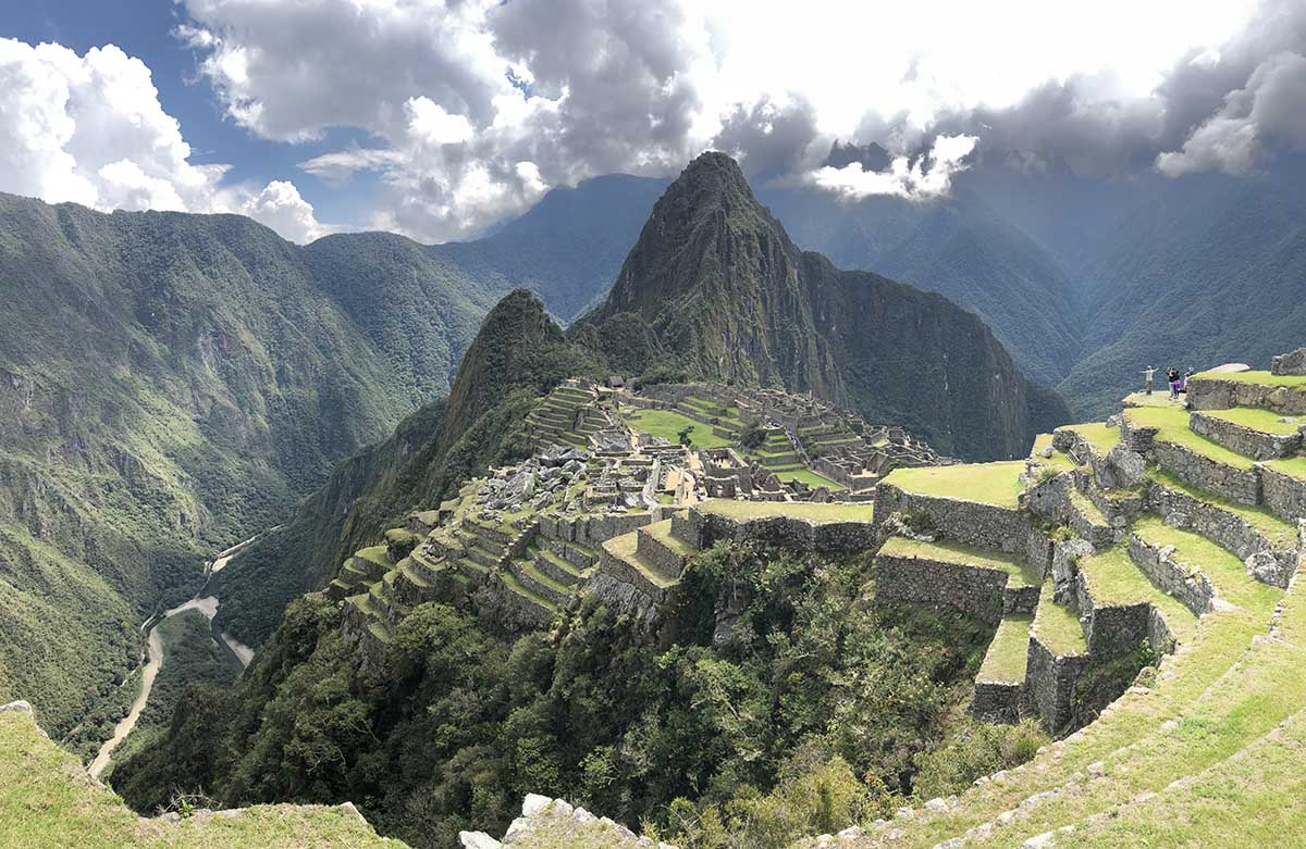 The view of Machu Picchu showing the layered terraces, Huayna Picchu and the cloudy sky. This view is more encompassing of the entire Machu Picchu ruins, mountains and the river below.