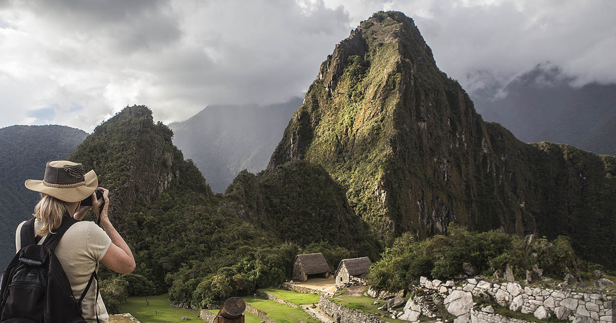 A tourist in a hat takes a photo of Huayna Picchu Mountain in the glowing light.