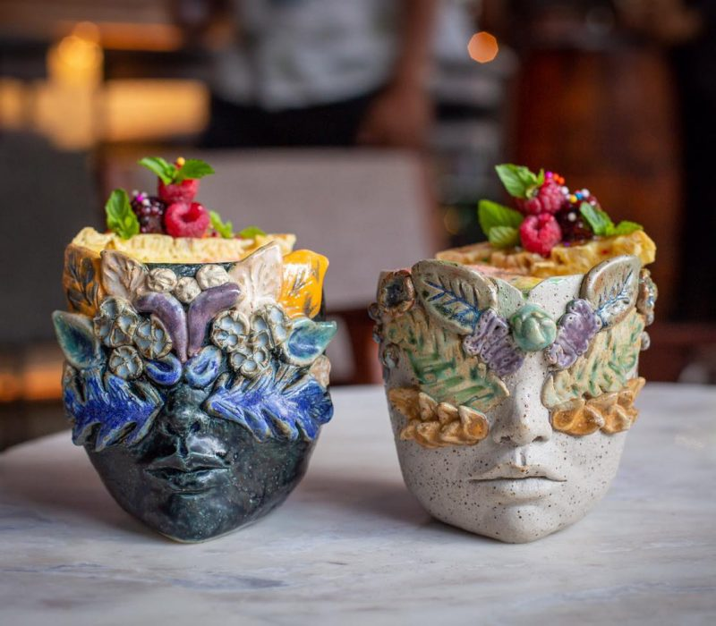 Two handmade cups holding the Mardi Gras cocktail at Carnaval Bar in Lima, Peru. Cups in the shape of faces with floral design. Assorted fruit atop the beverage.