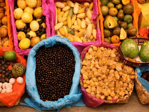 Assorted fruits in baskets at a Peruvian market. Many markets in Peru sell the ingredients in this Peruvian food glossary.