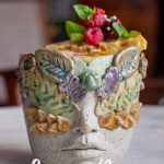 ceramic cup with face and leaves molded into the front part of the cup. Slice of pineapple with rasberries on top sticks out of the cup. 10 Best Bars in Lima, Peru written in white on top of photo