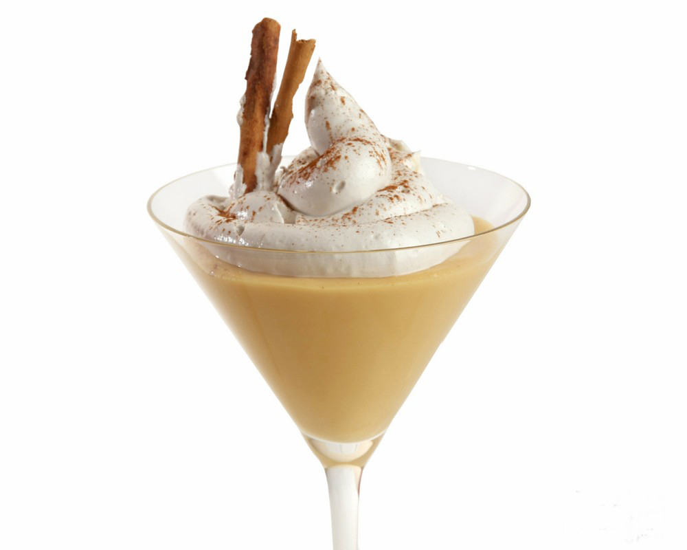A glass cup with the yolky Peruvian dessert suspiro a limeña, topped with whipped cream and cinnamon