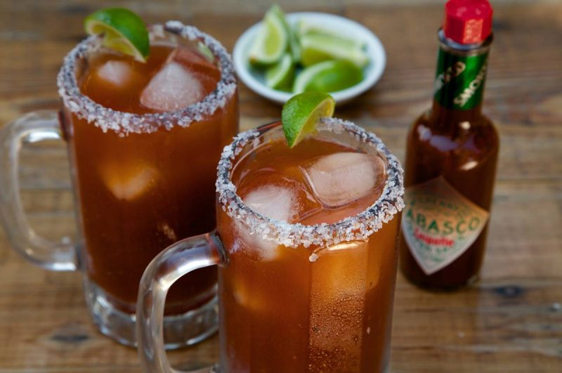 Two tall glasses with orange beverage inside. Salted rims and lime wedge on top. Bottle of tabasco hot sauce and bowl with more lime in background.