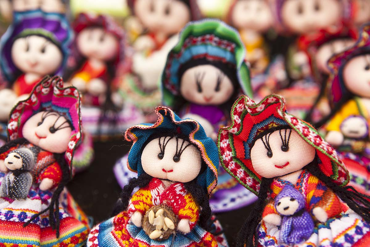 Andean dolls wearing traditional woven skirts, shawls, and hats with black bead eyes.