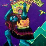 Street art image of blue woman wearing traditional Peruvian skirt carrying a house on her shoulders.