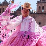 Native Andean woman dancing in traditional pink dress with white and pink fringe shawl and a tan bowler hat in front of a colonial style church