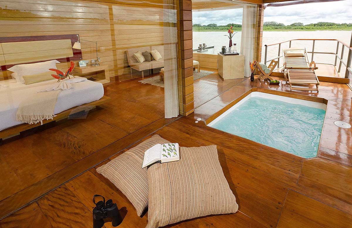 A cruise cabin with king bed, plunge pool, sitting area, and view of the Amazon River in Iquitos