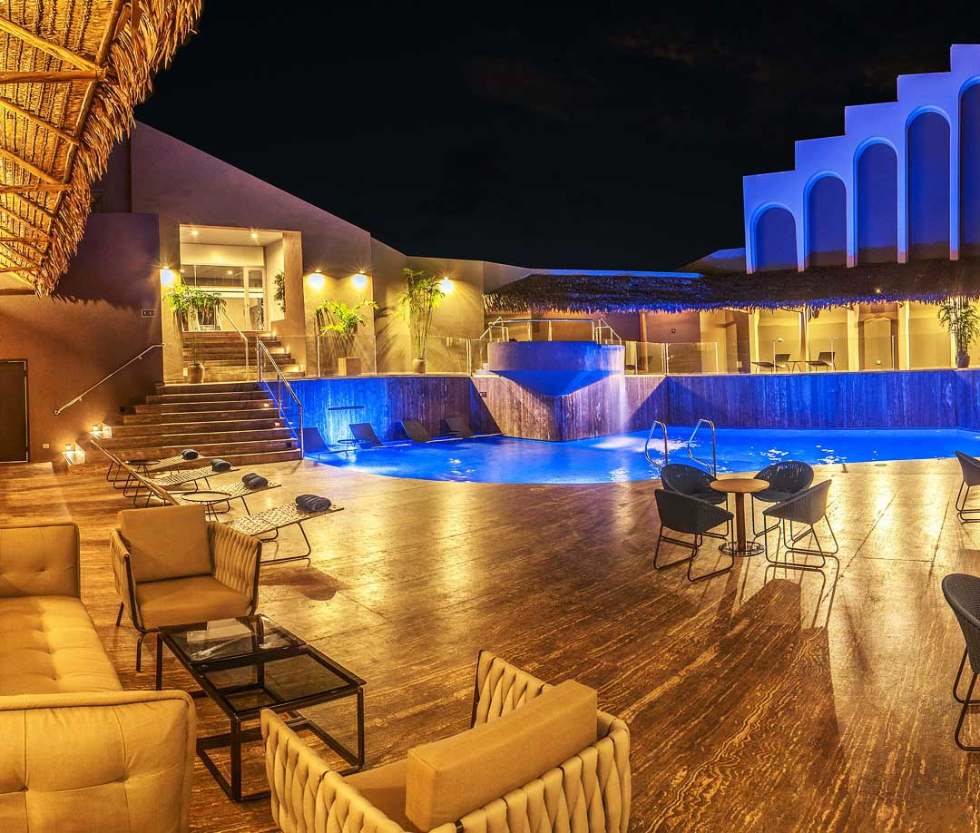 The rooftop pool area at the DoubleTree by Hilton hotel in Iquitos, Peru lit up at night.