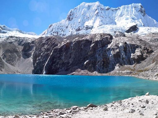 View of Laguna 69, a clear blue-green lake surrounded by snow-capped mountains and clear blue skies