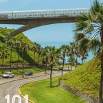 bridge with road beneath leading towards the ocean surrounded by green grass and palm trees and the text 101 things to do in Lima in the left bottom corner