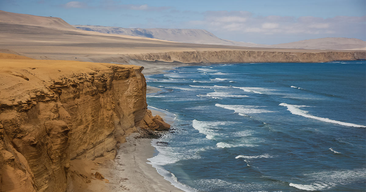 Waves crashing against the expansive desert cliff coast of the Paracas National Reserve in Peru.
