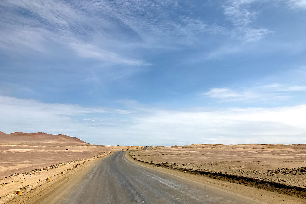 Hard-packed dirt road in the Paracas National Reserve surrounded by expansive desert.