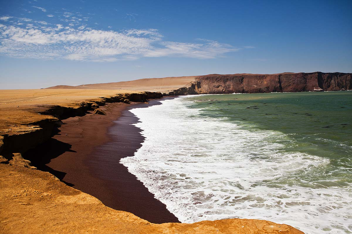 The crescent shaped Playa Roja with red sand in the Paracas National Reserve in Peru.