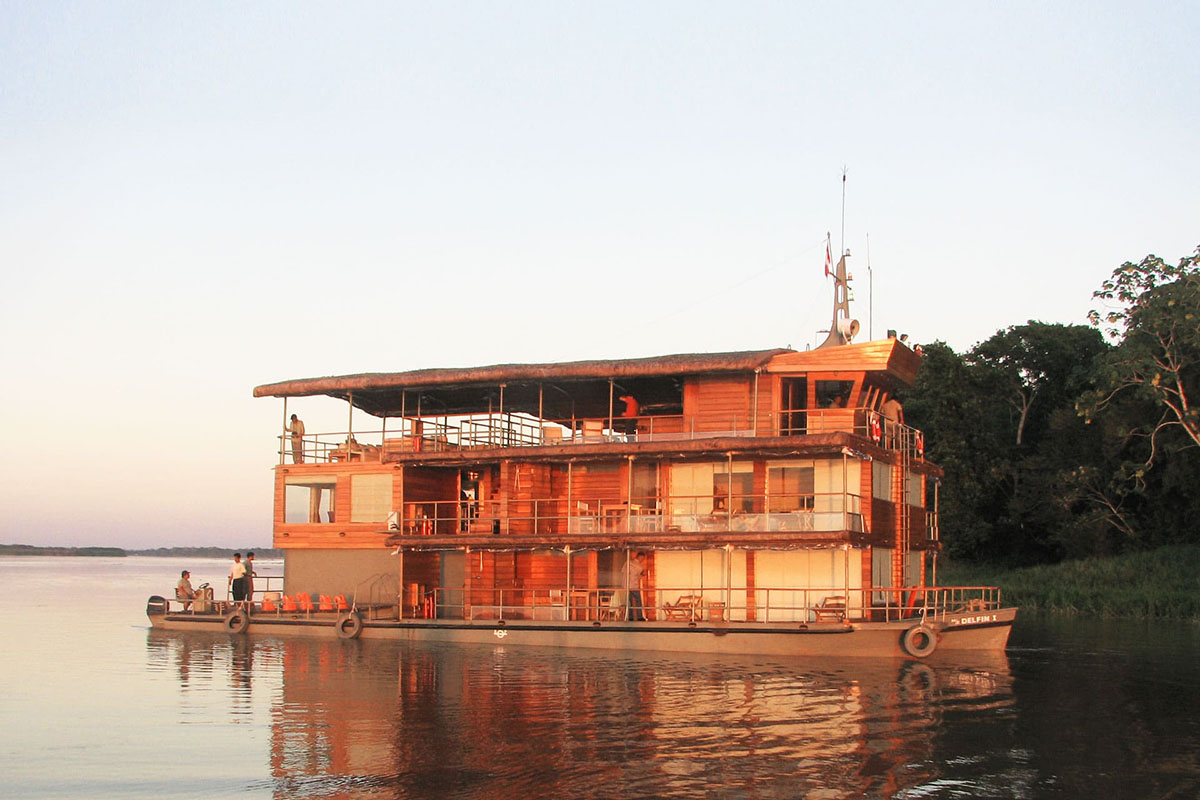 The three story Delfin Amazon river cruise sits on the still Amazon River at dusk.