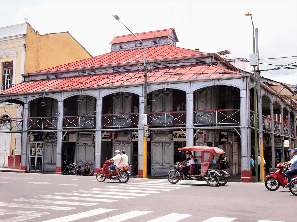 2 men riding a motorcycle in front of concrete building in Iquitos, Peru