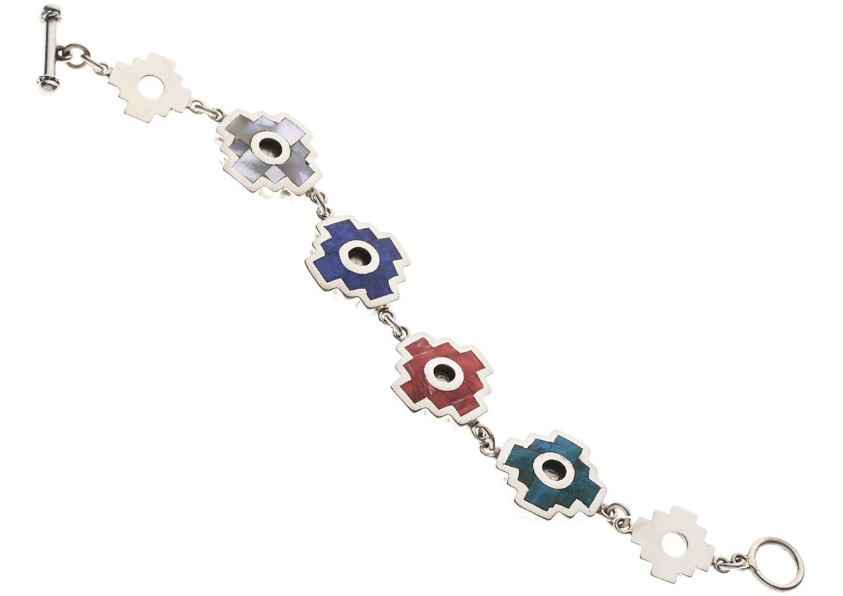 A silver chakana bracelet with gray, blue, red, and turquoise stone inlays.