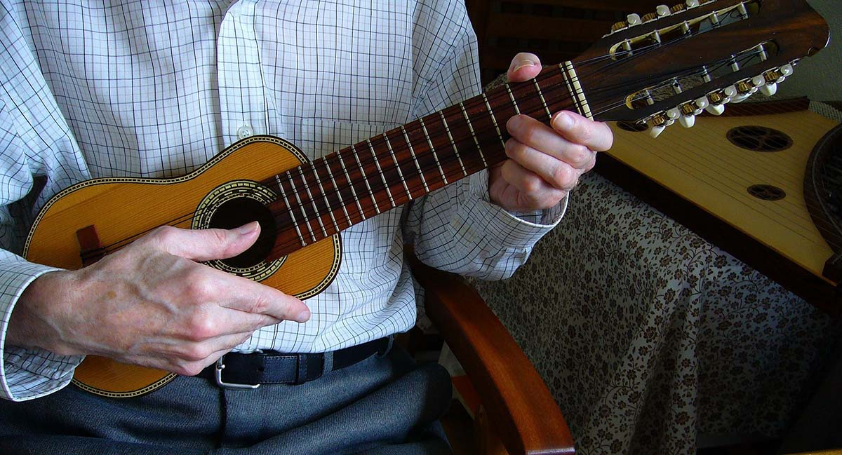 A man plays a charango, a small stringed instrument with ten strings.