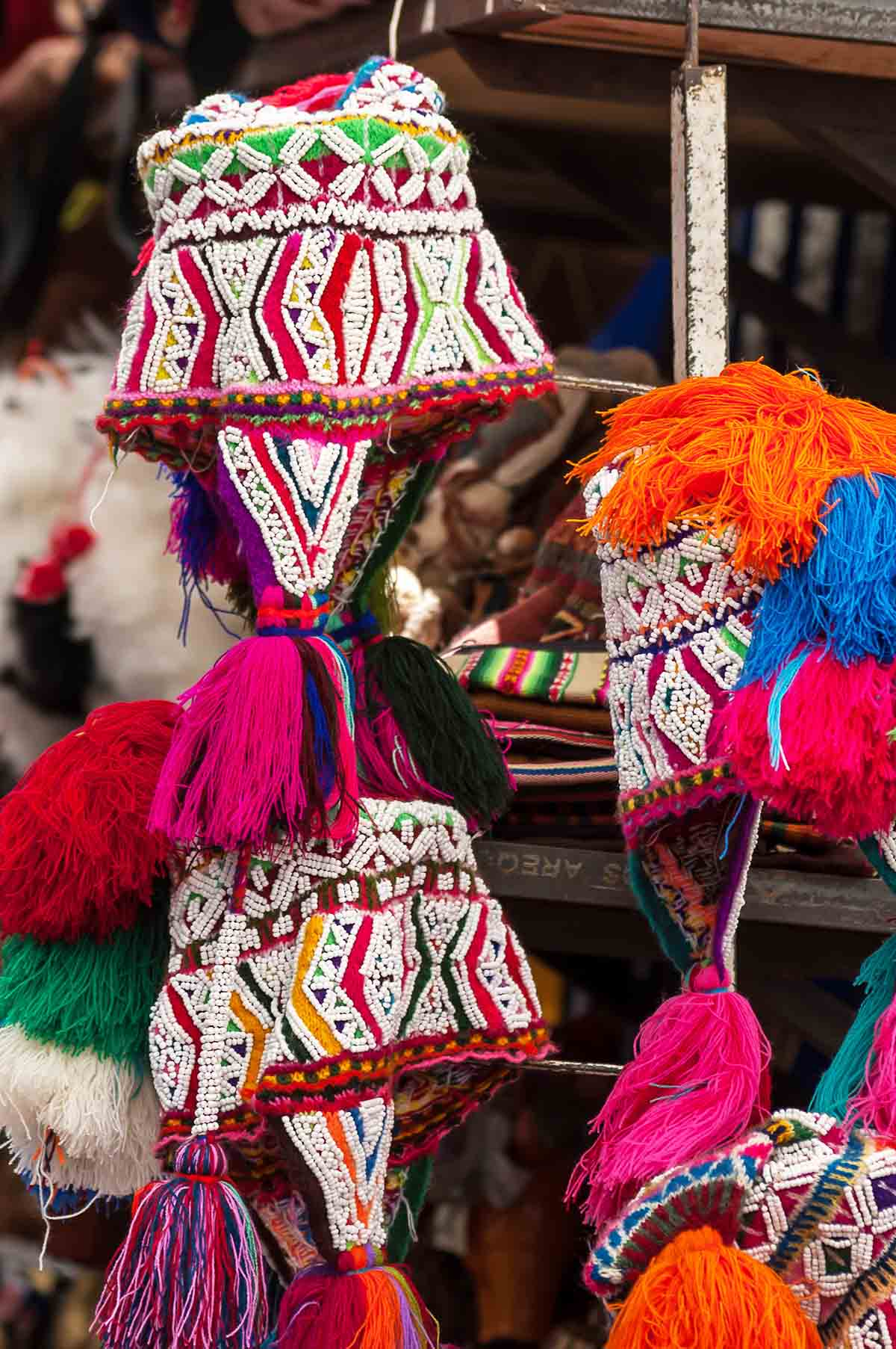 Bright red, yellow, and green chullos with white beading and tassels.