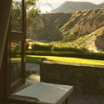 A coffee cup on an open windowsill with green valley and canyon in the warm morning sunlight behind