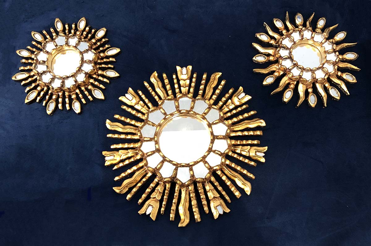 Three decorative Peruvian mirrors in a golden Inca sun style.