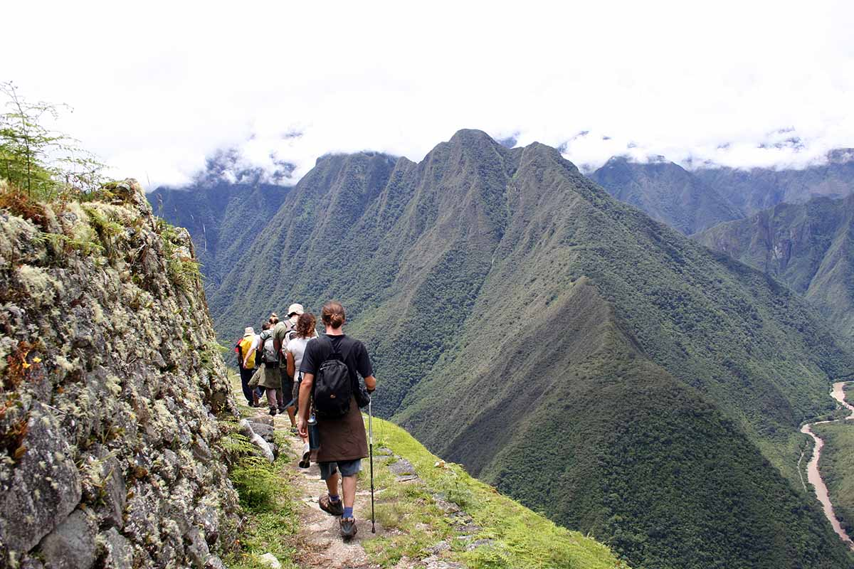 Hikers walking along a narrow path on the Inca Trail with green mountains behind.