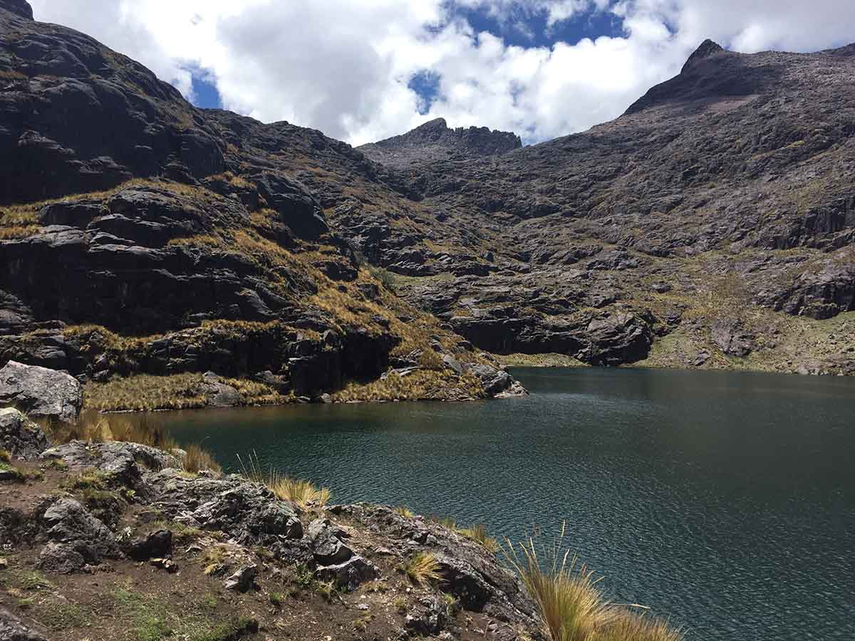 A blue lagoon surrounded by brown hills on the Lares Trek.