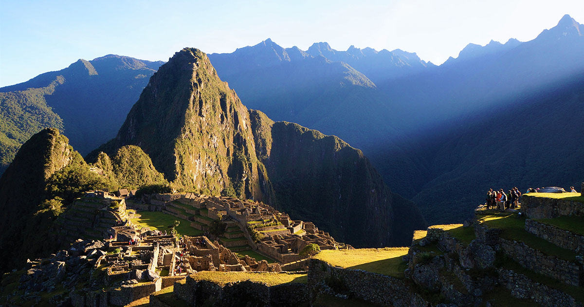 Machu Picchu ruins bathed in sunlight as a group of tourists overlook the ruins.