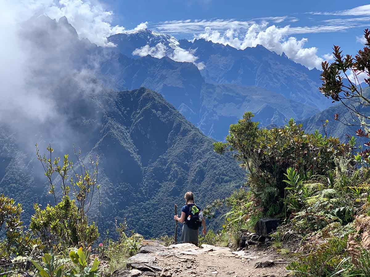 Hiker walking down a path in Machu Picchu with mountains and clouds towering in the background.