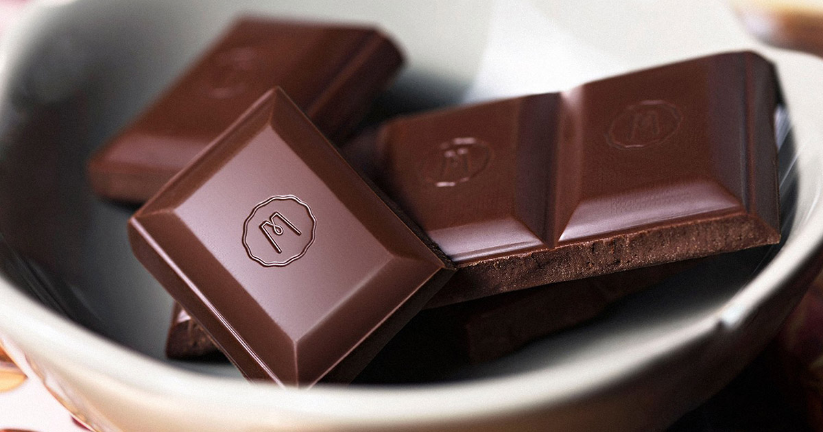 White bowl filled with squares of dark Marana Chocolate, one of many chocolate brands in Peru