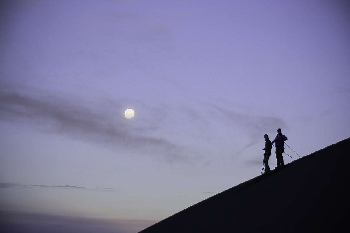 Silhouette of two hikers walking down a volcano in the Salinas and Aguada Blanca National Reserve.