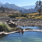 a couple sit in a natural turquoise hot spring pool with a mountain canyon in the background