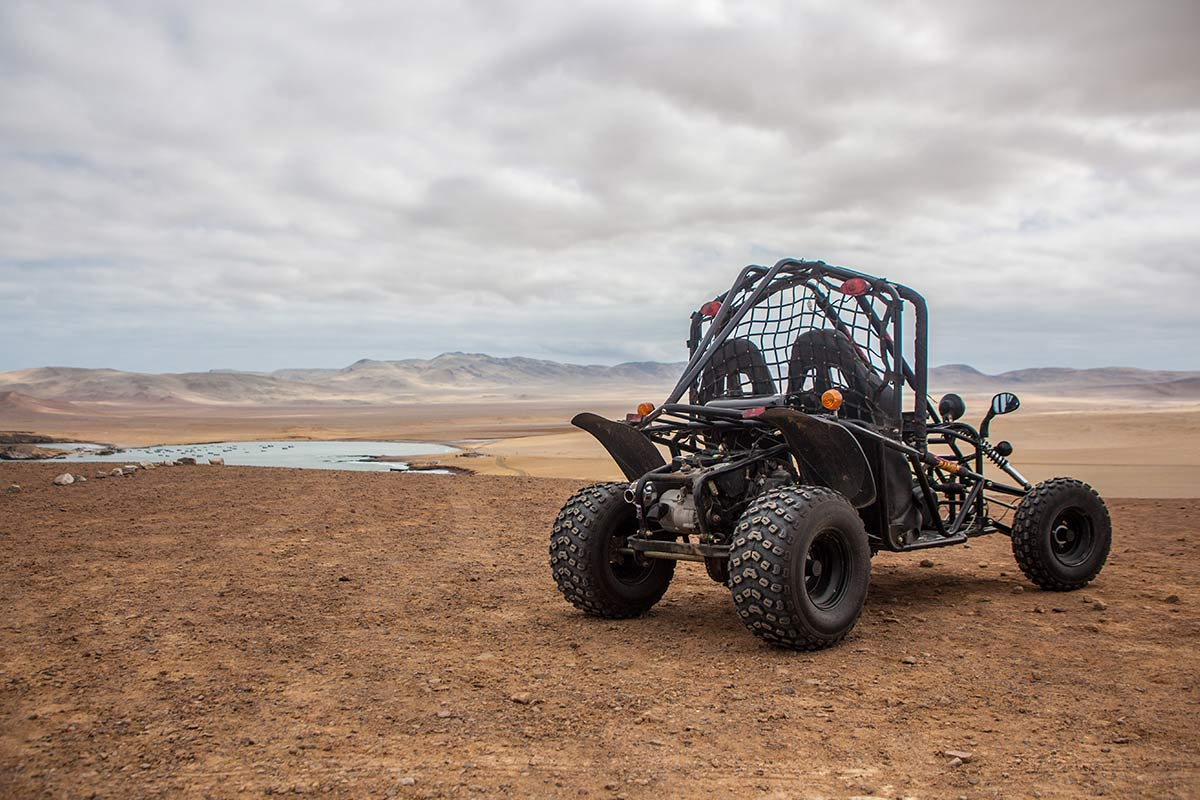 An open air quad bike parked on a hill overlooking the Paracas Peninsula on a cloudy day.