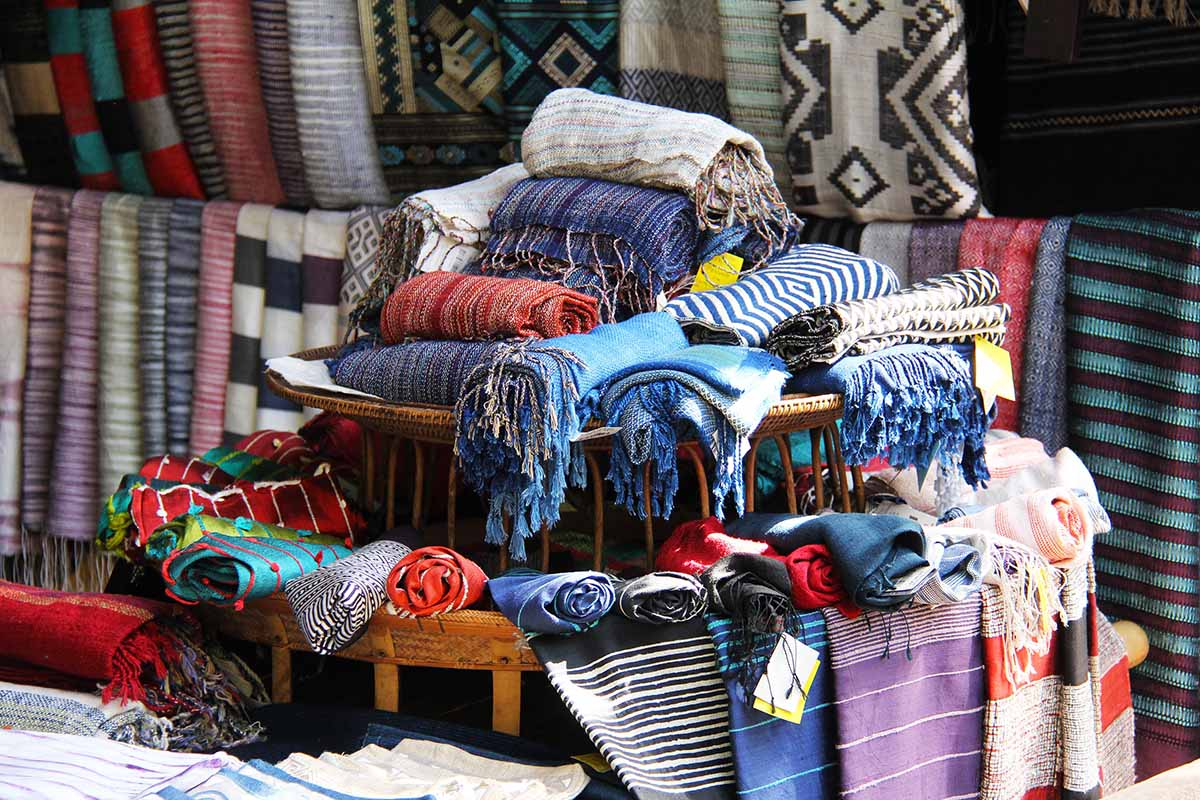Scarves made out of alpaca wool in a Peruvian market. Colors include whites, blues, reds, and purples.